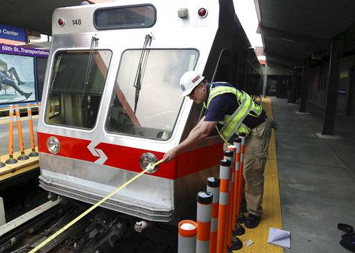 In this photo released via Twitter by the National Transportation Safety Board, NTSB investigator Rick Downs takes measurements at scene of a commuter rail accident Tuesday, Aug. 22, 2017, in Upper Darby, Pa. An inbound train crashed into the rear of the parked train, pictured, at the suburban Philadelphia terminal early Tuesday morning, injuring dozens of passengers and the train's operator. (National Transportation Safety Board via AP)