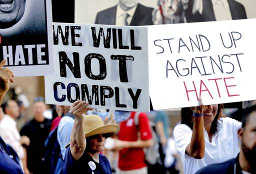 People protest outside the Phoenix Convention Center, Tuesday, Aug. 22, 2017, in Phoenix. Protests were held against President Donald Trump as planned to host a rally inside the convention center. (AP Photo/Matt York)