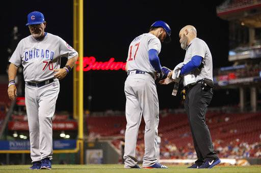 Chicago Cubs' Kris Bryant (17) hands off his equipment before heading into the clubhouse for X-rays after being hit by a pitch from Cincinnati Reds relief pitcher Drew Storen during the ninth inning of a baseball game, Tuesday, Aug. 22, 2017, in Cincinnati. At left is Cubs managers Joe Maddon. (AP Photo/John Minchillo)
