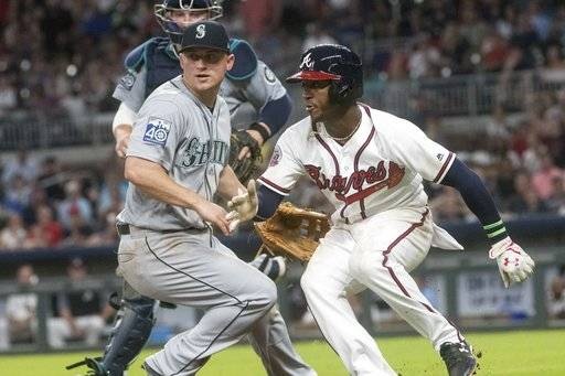 Atlanta Braves' Ozzie Albies, right, hits the brakes in a rundown as Seattle Mariners third baseman Kyle Seager defends during the sixth inning of a baseball game, Tuesday, Aug. 22, 2017, in Atlanta. Albies scored on the play. (AP Photo/John Amis)