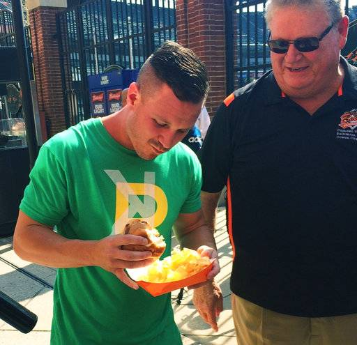 Former Baltimore Orioles slugger Boog Powell watches Oakland Athletics leadoff hitter Boog Powell eat a pork sandwich from Boog's BBQ by the food stand outside Oriole Park at Camden Yards before the Athletics play the Orioles in Baltimore on Tuesday, Aug. 22, 2017. The name's the same, and they're both known for playing baseball. It's a bit early, however, to start comparing their home run swings. (AP Photo/David Ginsburg)
