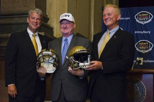 Chet Gladchuk, Navy athletic director, Philadelphia Mayor Jim Kenney, and Boo Corrigan, West Point athletic director are shown Tuesday, Aug. 22, 2017. The Army-Navy football game will be played in Philadelphia four times from 2018-2022, returning to its most frequent host city. The academies announced Tuesday at Philadelphia's City Hall that Lincoln Financial Field, home of the NFL's Eagles, will be the site of the 2018, '19, '20 and '22 Army-Navy games.(Joy Lee/The Philadelphia Inquirer via AP)