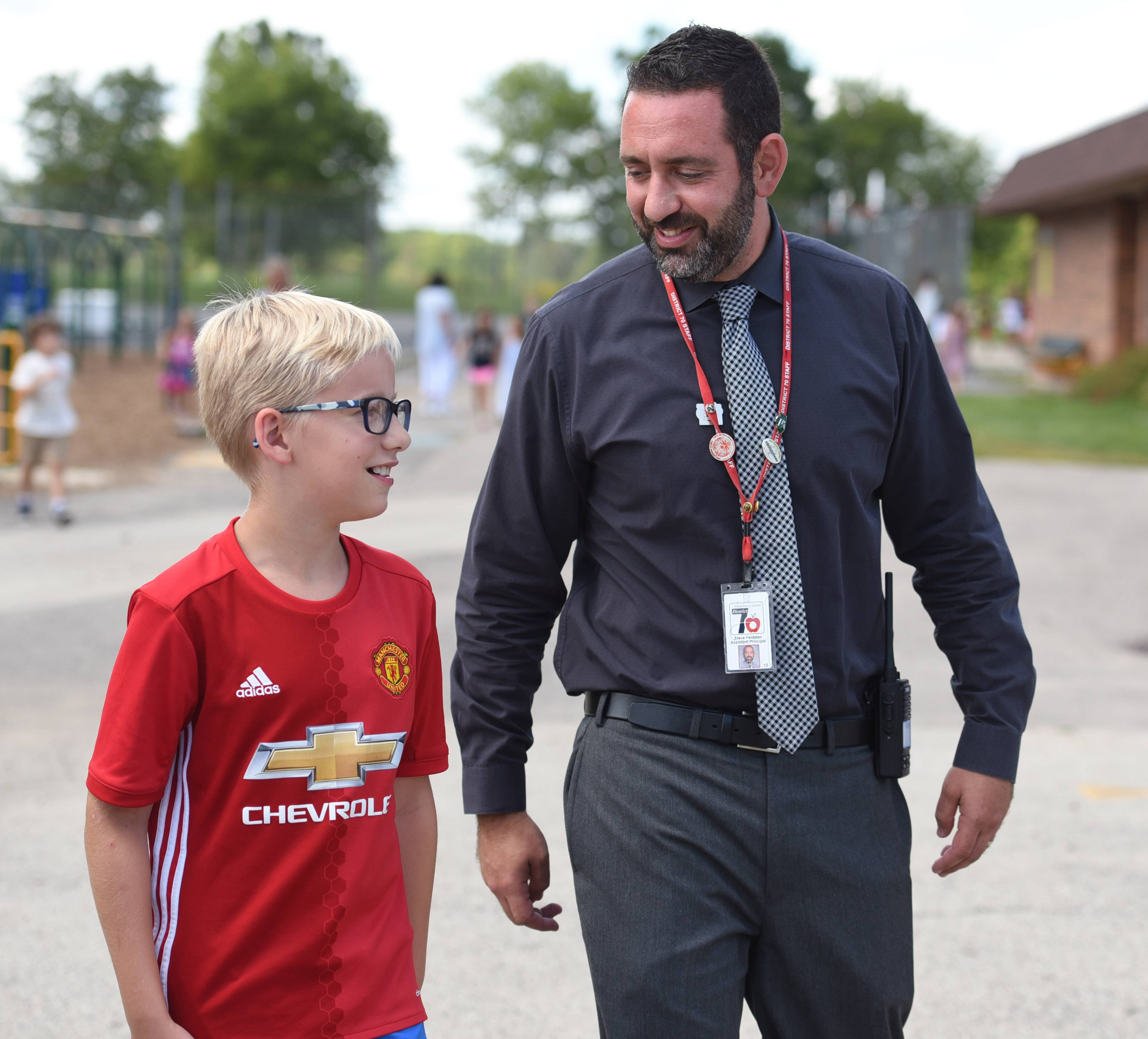 New Butterfield School Assistant Principal Steve Feldman talks with fifth-grade student Noah Dalsgaard after recess Wednesday, the first day of classes in Libertyville School District 70.