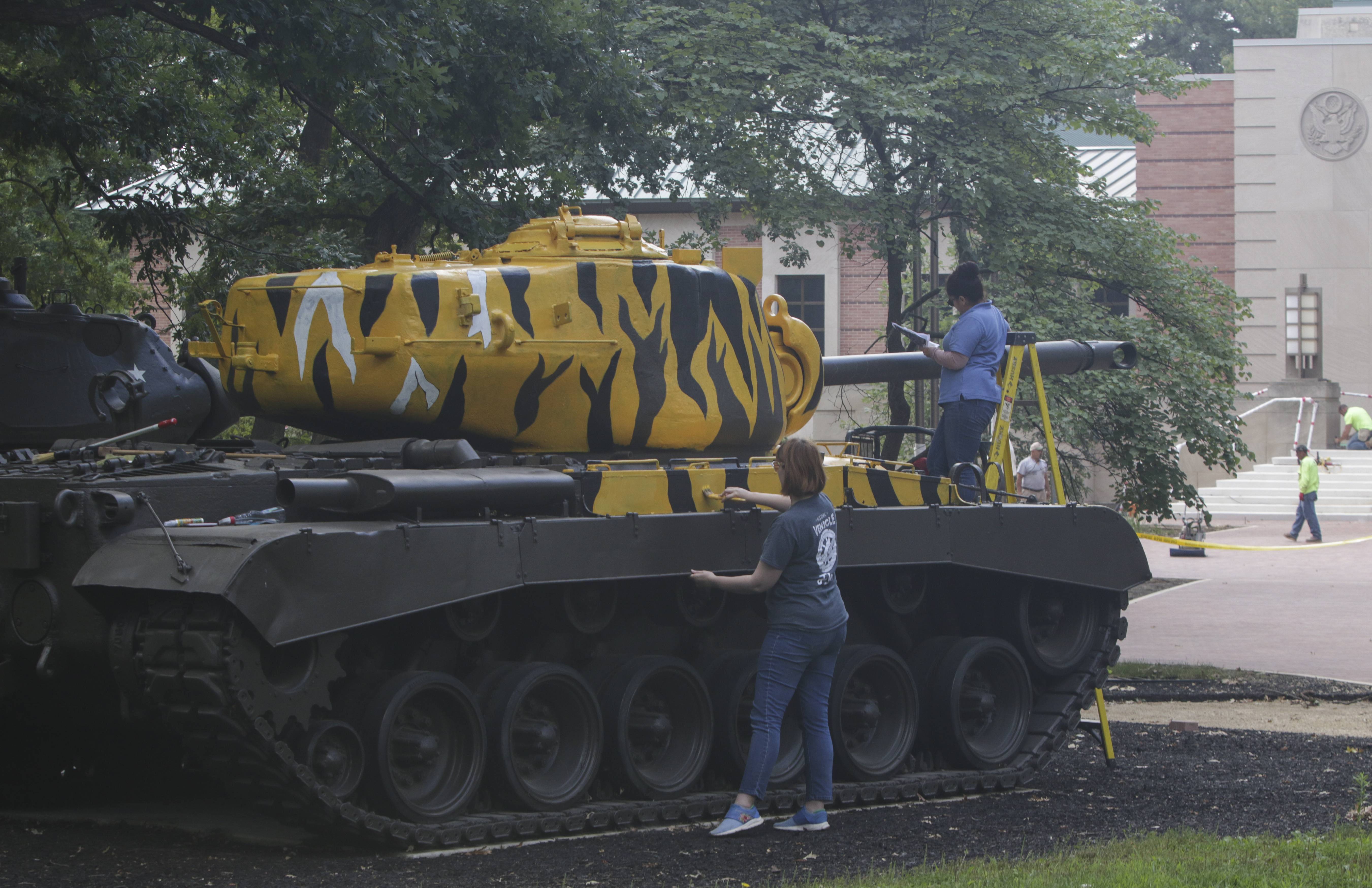 Employees repaint the tiger stripes on a Korean War tank in a park updated with new landscaping and paths outside the First Division Museum.