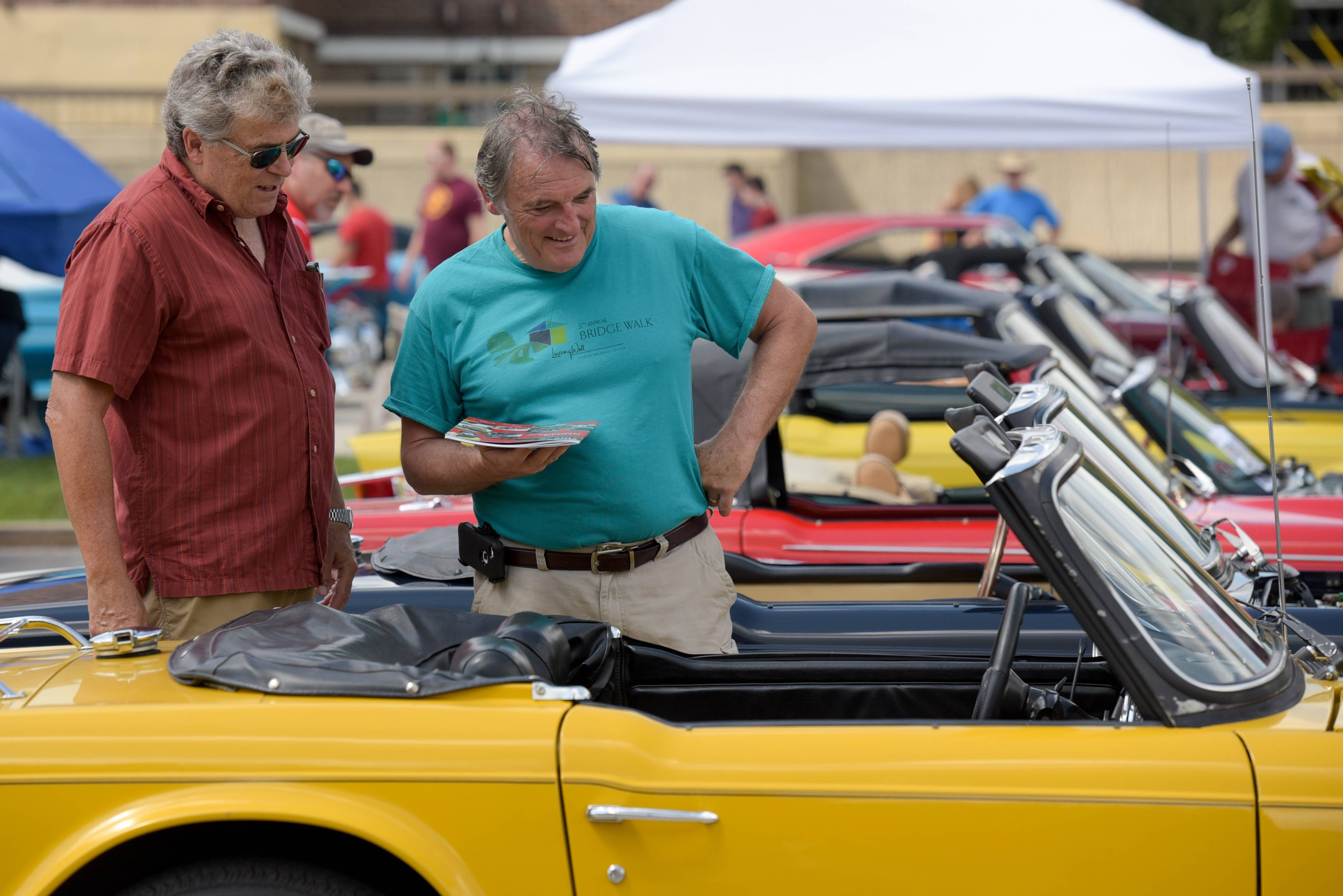 Neighbors Mike Garcia and Greg Giel from Geneva check out a classic Triumph at last year's Concours d'Elegance in downtown Geneva.