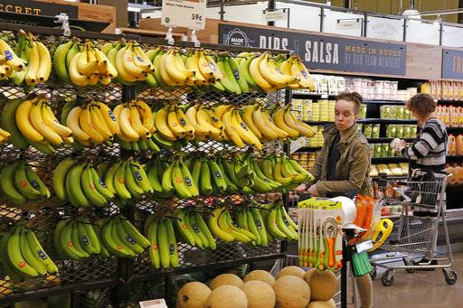 FILE - In this May 3, 2017, file photo, customers shop at a Whole Foods Market in Upper Saint Clair, Pa. Amazon is moving swiftly to make big changes at Whole Foods, saying it plans to cut prices on bananas, eggs, salmon, beef and more as soon as it completes its $13.7 billion takeover. (AP Photo/Gene J. Puskar, File)