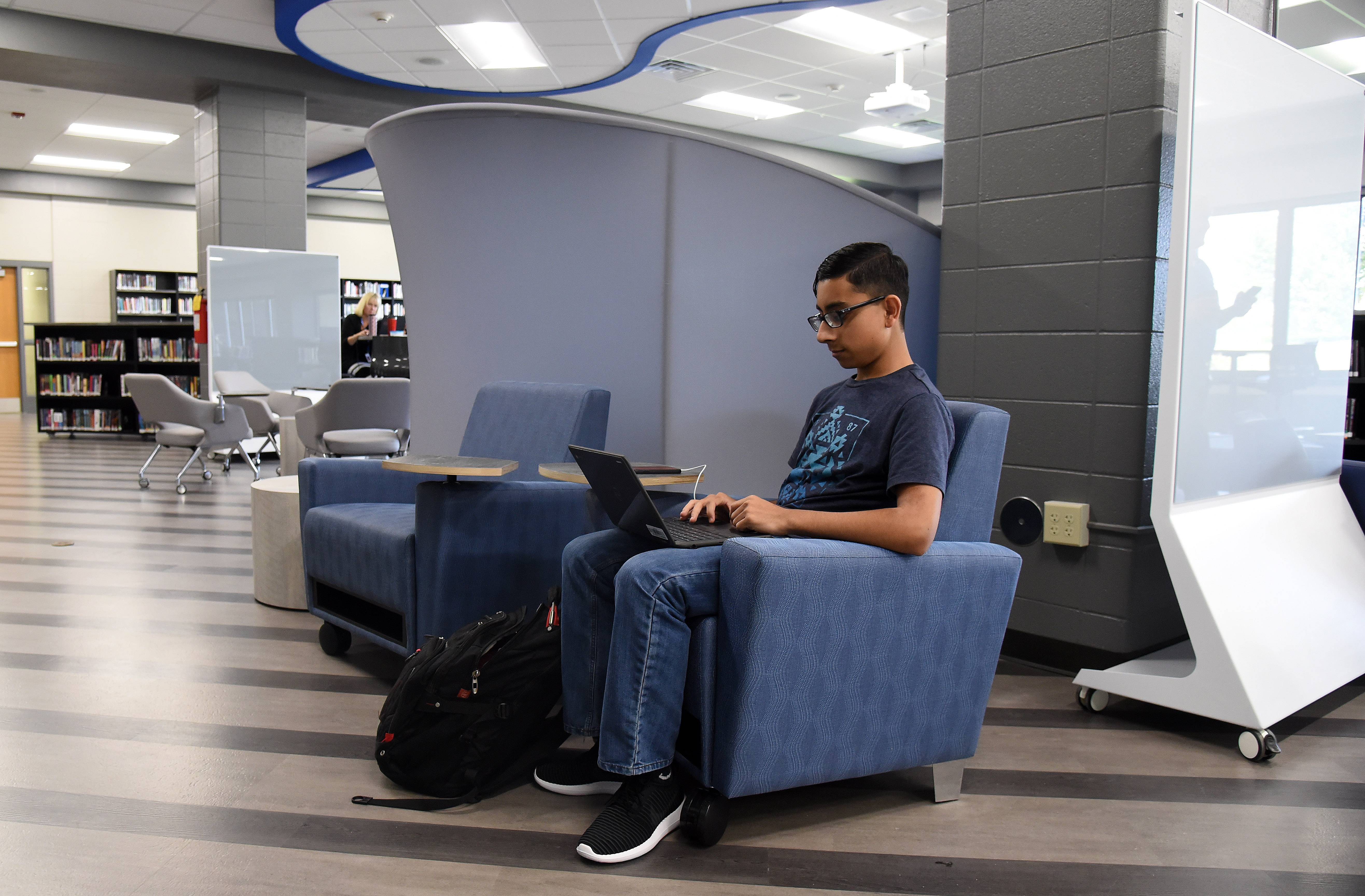 Senior Shaaz Syed works in Central High School's recently remodeled library media center Wednesday in Burlington. The school debuted new facilities this week, including new classrooms and modern weight training and cardio fitness areas.