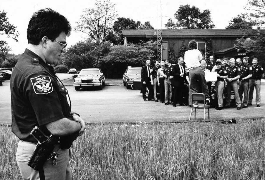 In this 1989 photo, 15 members of the Barrington Hills Police Department prepare to have a photo taken after winning an $8.3 million lottery jackpot as officer Dominic Caputo, who wasn't among the winners, stands aside. Caputo was on his honeymoon and didn't chip in for that week's office pool. He continued to work as a Barrington Hills police officer until being injured on the job in a head-on car crash in 2016.