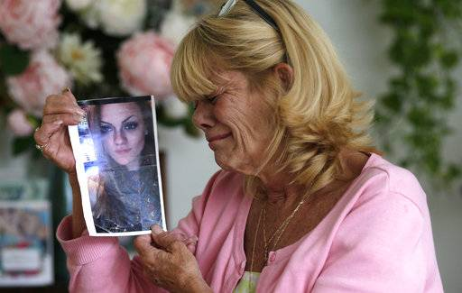 "In this Thursday, July 13, 2017 photo, Michelle Holley holds a photograph of her daughter Jaime Holley, 19, who died of a heroin overdose in November 2016, at her home in Fort Lauderdale, Fla. The Reflections treatment center looked like just the place for her youngest daughter to kick heroin. ""It looked fine. They were saying all the right things to me. I could not help my child so I trusted them to help my child,� Holley said. Instead, the center refused to give 19-year-old Jaime Holley her prescription medicine when she left, forcing her to use illegal drugs to avoid acute withdrawal symptoms, her mother said. (AP Photo/Lynne Sladky)"