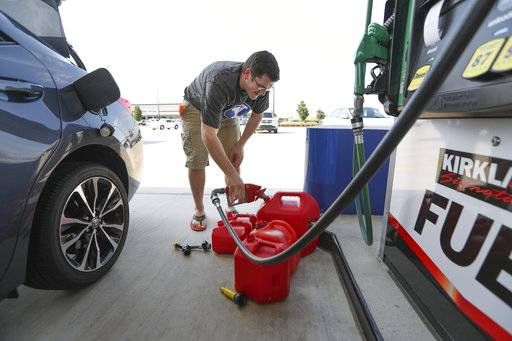 Chris Mathew fills his vehicle and five gas cans at Costco in preparation for tropical weather on Wednesday, Aug. 23, 2017, in Pearland, Texas. The U.S. National Hurricane Center said the tropical depression was expected to intensify over the warm waters of the Gulf of Mexico before reaching the Texas coast Friday. (Steve Gonzales/Houston Chronicle via AP)
