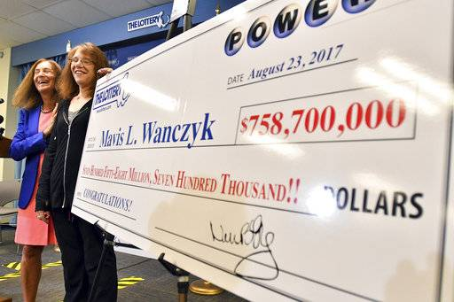 Mavis Wanczyk, of Chicopee, Mass., stands by a poster of her winnings during a news conference where she claimed the $758.7 million Powerball prize at Massachusetts State Lottery headquarters, Thursday, Aug. 24, 2017, in Braintree, Mass. Officials said it is the largest single-ticket Powerball prize in U.S. history. At left is state treasurer Deb Goldberg. (AP Photo/Steven Senne)