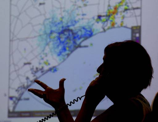 A map of the Texas Coast is projected on a screen as Deb Nowinski, a disability integration coordinator, gives information to a caller regarding the approach of Hurricane Harvey at the Galveston County Office of Emergency Management Emergency Operations Center in Dickinson, Texas, Thursday, Aug. 24, 2017. (Stuart Villanueva/The Galveston County Daily News via AP)