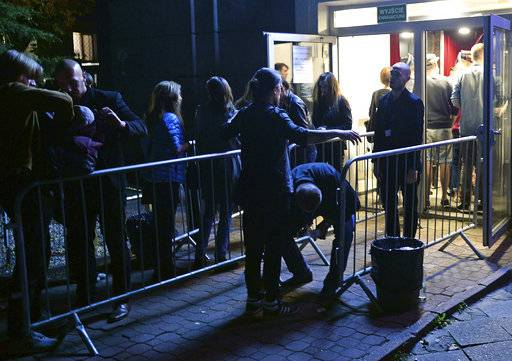Spectators are checked by security guards as the enter a club for a concert by the American Allah-Las rock band, in Warsaw, Poland, Thursday, Aug. 24, 2017. The band's concert in Rotterdam, The Netherlands was cancelled at the last minute by the police on Wednesday due to a terror threat. (AP Photo/Alik Keplicz)