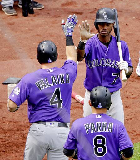 Colorado Rockies' Pat Valaika (4) celebrates with teammates after hitting a two-run home run during the eighth inning of a baseball game against the Kansas City Royals Thursday, Aug. 24, 2017, in Kansas City, Mo. The Rockies won 3-2. (AP Photo/Charlie Riedel)