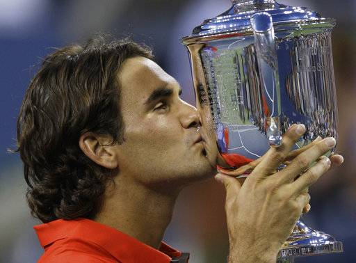 File-This Sept. 8, 2008 file photo shows Roger Federer, of Switzerland, kissing the championship trophy after winning the men's finals championship over Andy Murray, of Britain, at the U.S. Open tennis tournament in New York. Federer is back. All the way back. He's back at the U.S. Open after sitting it out a year ago. And he's back in the role of Grand Slam title contender after winning the past two majors he's entered, the Australian Open in January and Wimbledon in July. When the U.S. Open begins Monday, Aug. 28, 2017, Federer, at age 36 , will be among the men considered likeliest to win the championship, something he last did at Flushing Meadows nearly a decade ago. (AP Photo/Charles Krupa, File)
