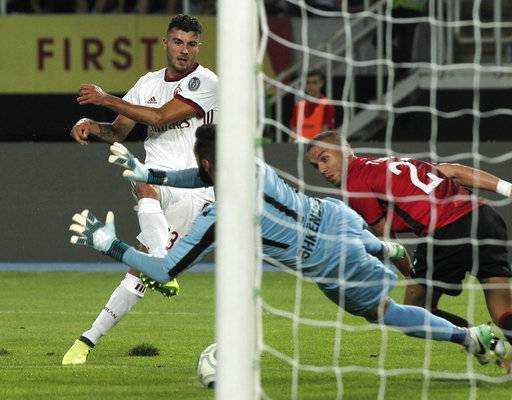 Milan's Patrick Cutrone, left, scores past Shkendija goalkeeper Kostandin Zahov, center, during their UEFA Europa League Playoff, second leg, soccer match, at Philip II Arena in Skopje, Macedonia, Thursday, Aug. 24, 2017. (AP Photo/Boris Grdanoski)