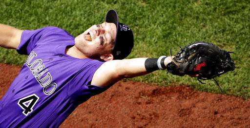 Colorado Rockies first baseman Pat Valaika catches a fly foul ball hit by Cheslor Cuthbert to end the sixth inning of a baseball game Thursday, Aug. 24, 2017, in Kansas City, Mo. (AP Photo/Charlie Riedel)