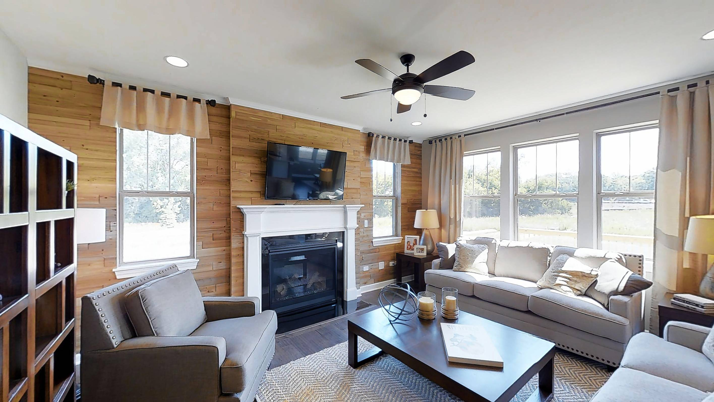 A fireplace against a rustic shiplap wall is the focal point of a family room