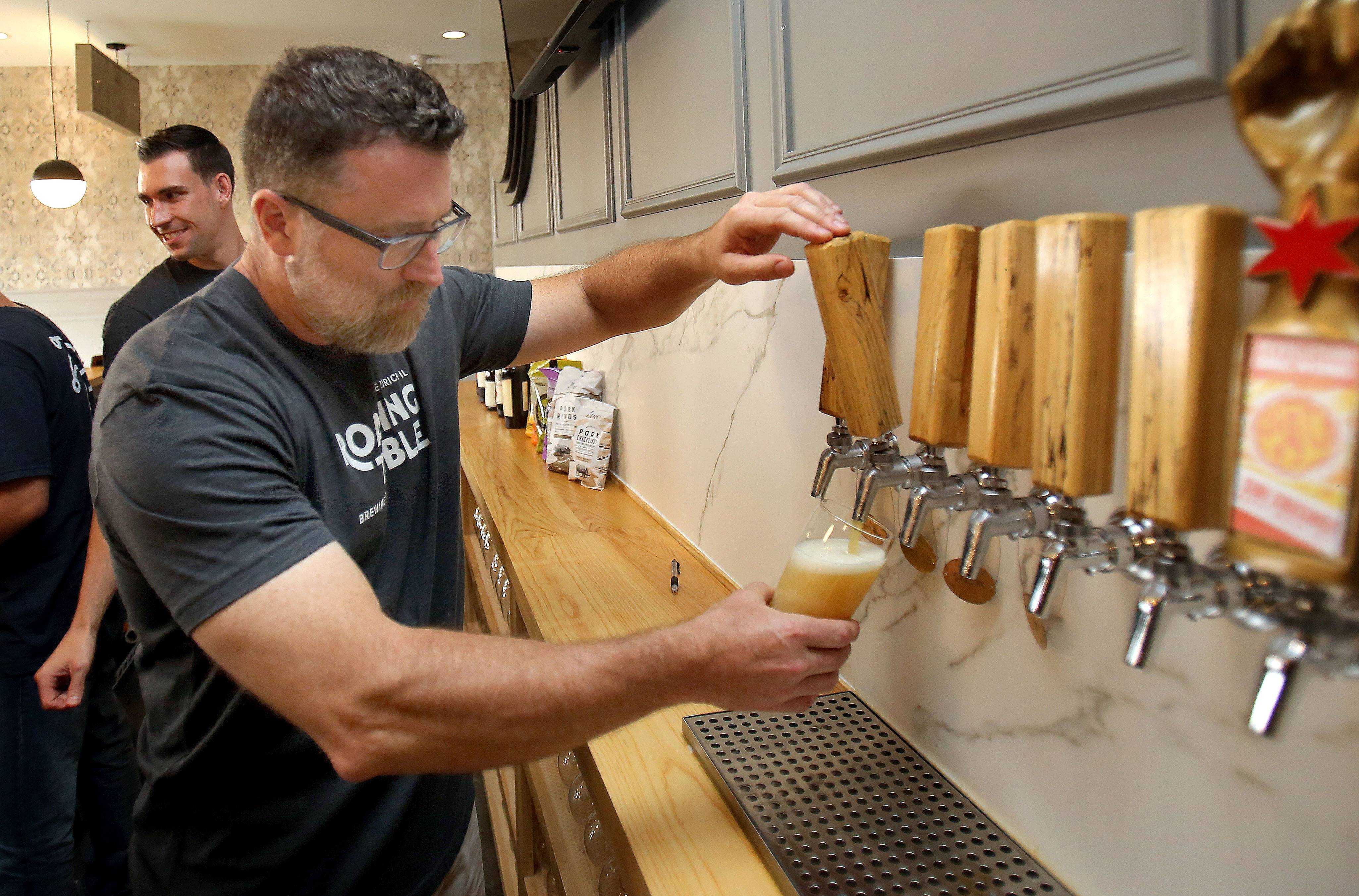 Owner and brewmaster Lane Fearing pours a beer Thursday at Roaring Table Brewery in Lake Zurich.