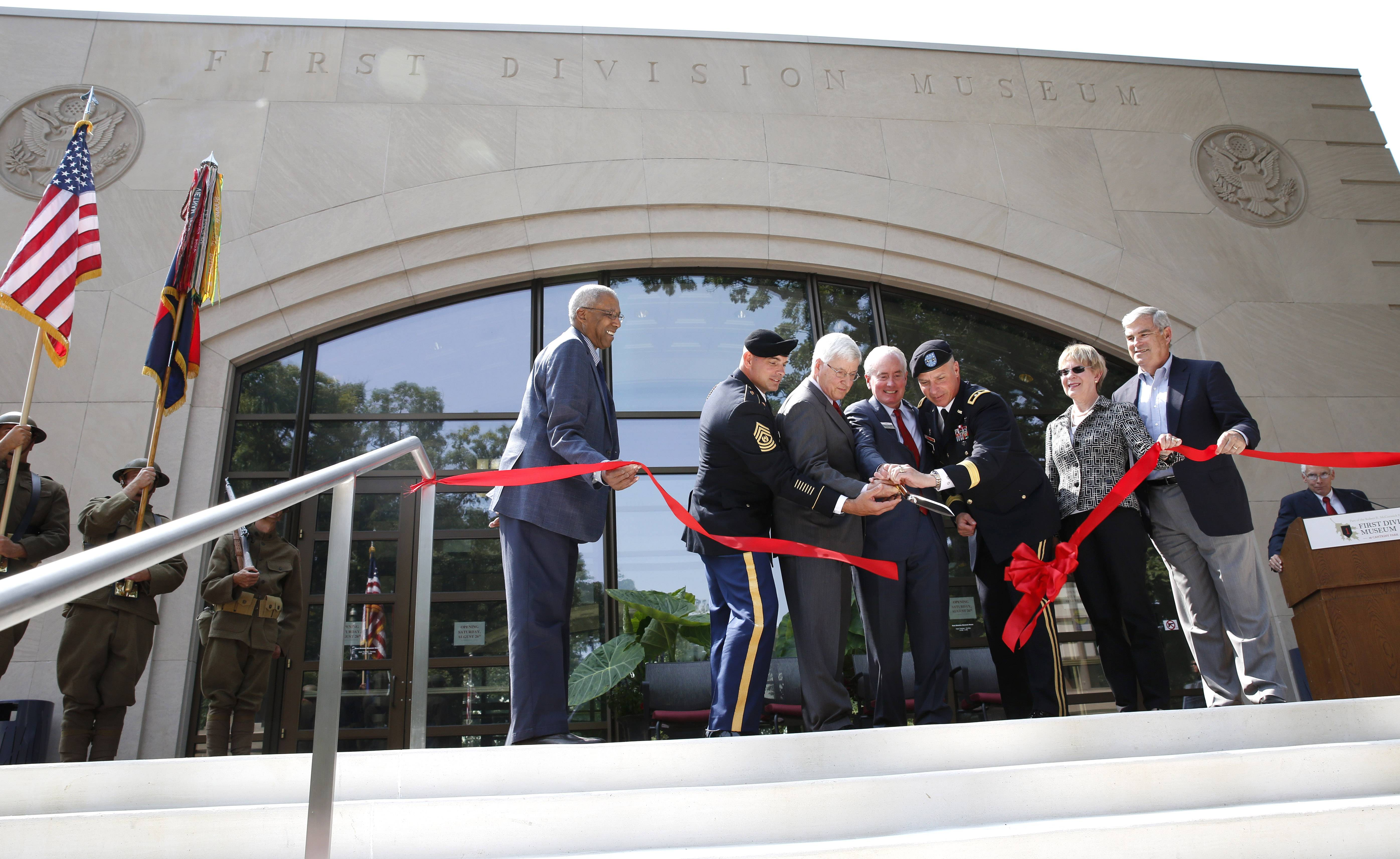 Dignitaries cut a red ribbon to officially reopen the First Division Museum on the grounds of Cantigny Park in Wheaton on Saturday. The museum had been closed since Veterans Day for an $8.5 million project to renovate exhibits and repair infrastructure. Luci Creative, a Lincolnwood design firm, was hired for the project.