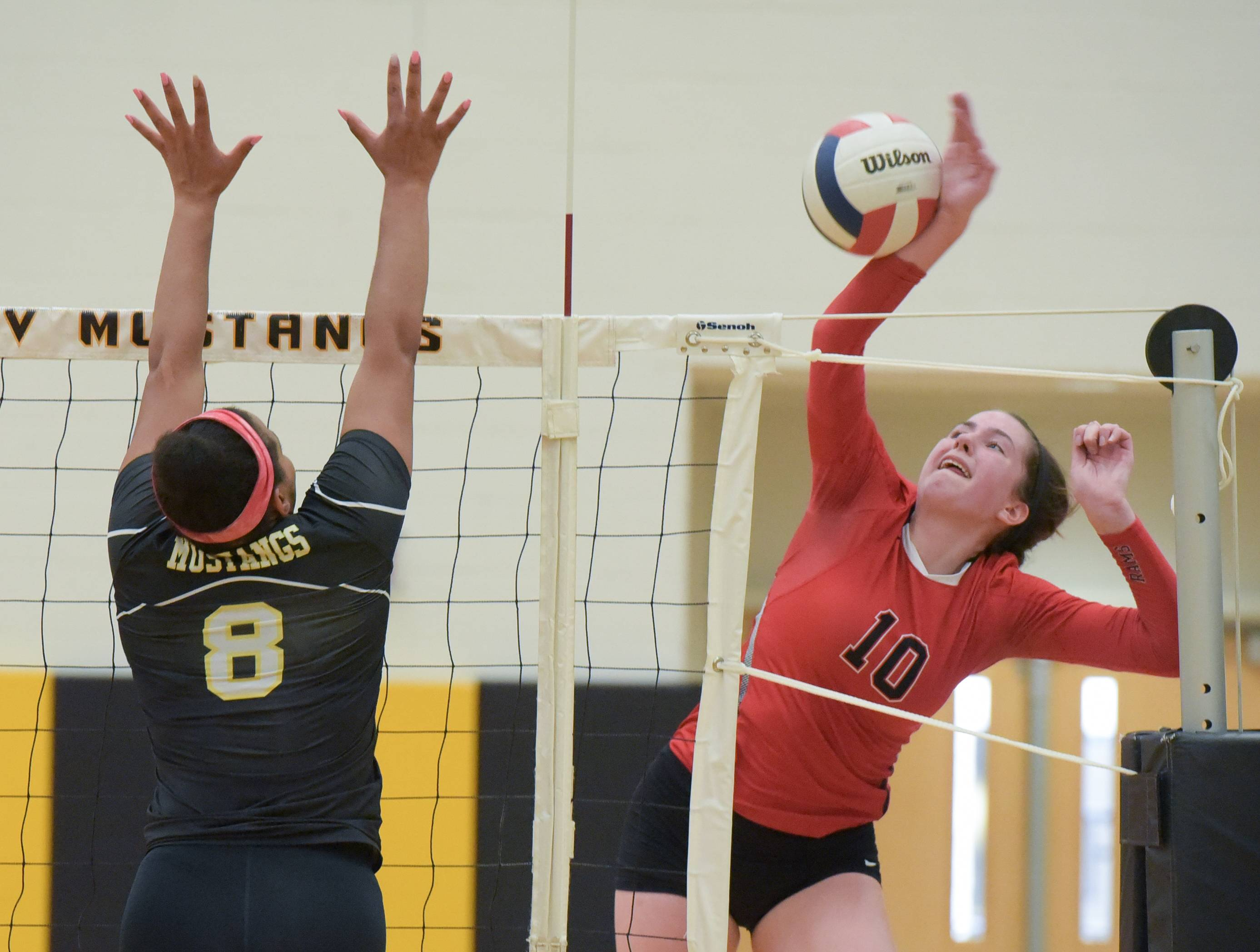 Glenbard East's Sarah Elliott (10) works to keep the ball in play as Metea Valley's Sydnee Marks (8) set up to block her shot during varsity girls volleyball on August 23, 2017.