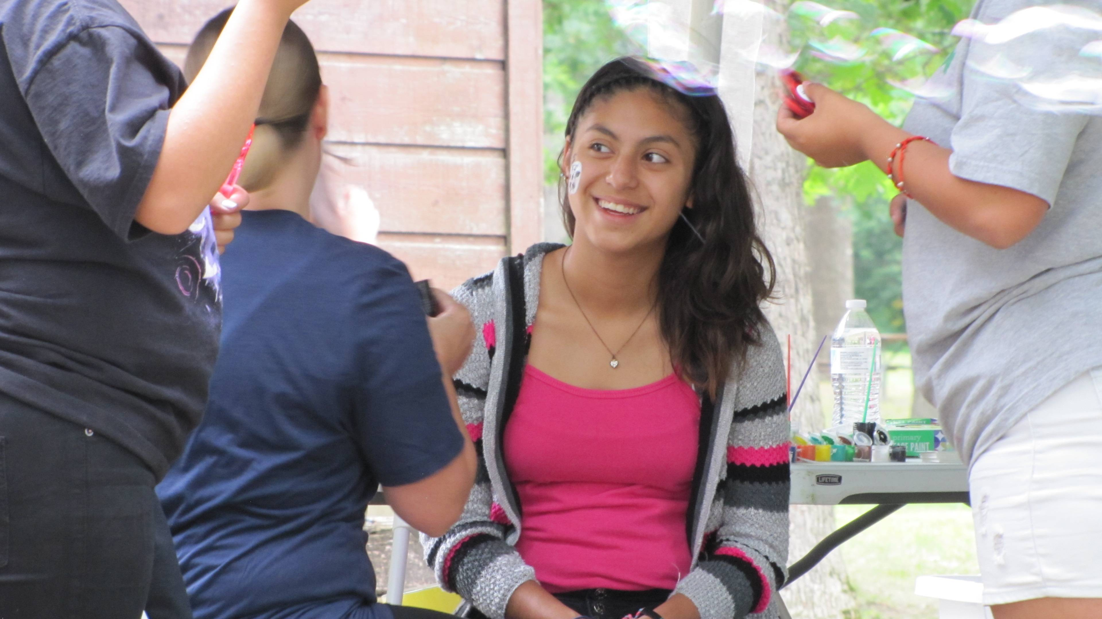 Marlene Banales, a player on Heart of the City's U12 Spartans team, gets her face painted at the cookout at Hinkston Park in Waukegan. Heart of the City