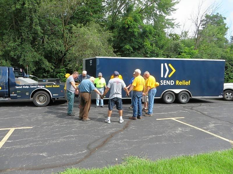 A group of volunteers from Southern Baptist Disaster Relief join in prayer before helping Lake County flood victims clean up earlier this month.