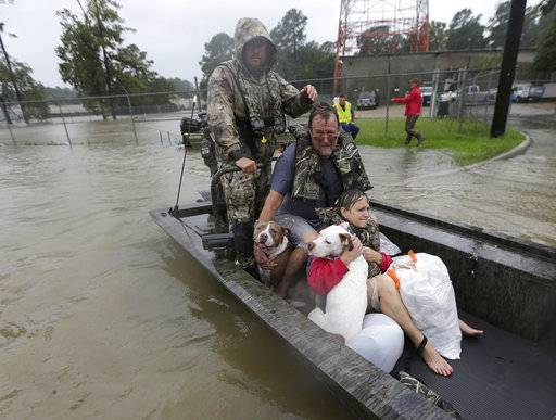 John and Cathy Cservek hold their dogs Lacy and Iggy while being rescued from their home as floodwaters from Tropical Storm Harvey rise Monday, Aug. 28, 2017, in Spring, Texas.