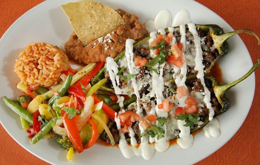 The Dos Amigos Chile Relleno is one large poblano pepper, cooked al dente, cut in half and stuffed with either meat or veggies and covered in cheese, sour cream, cilantro and tomato.