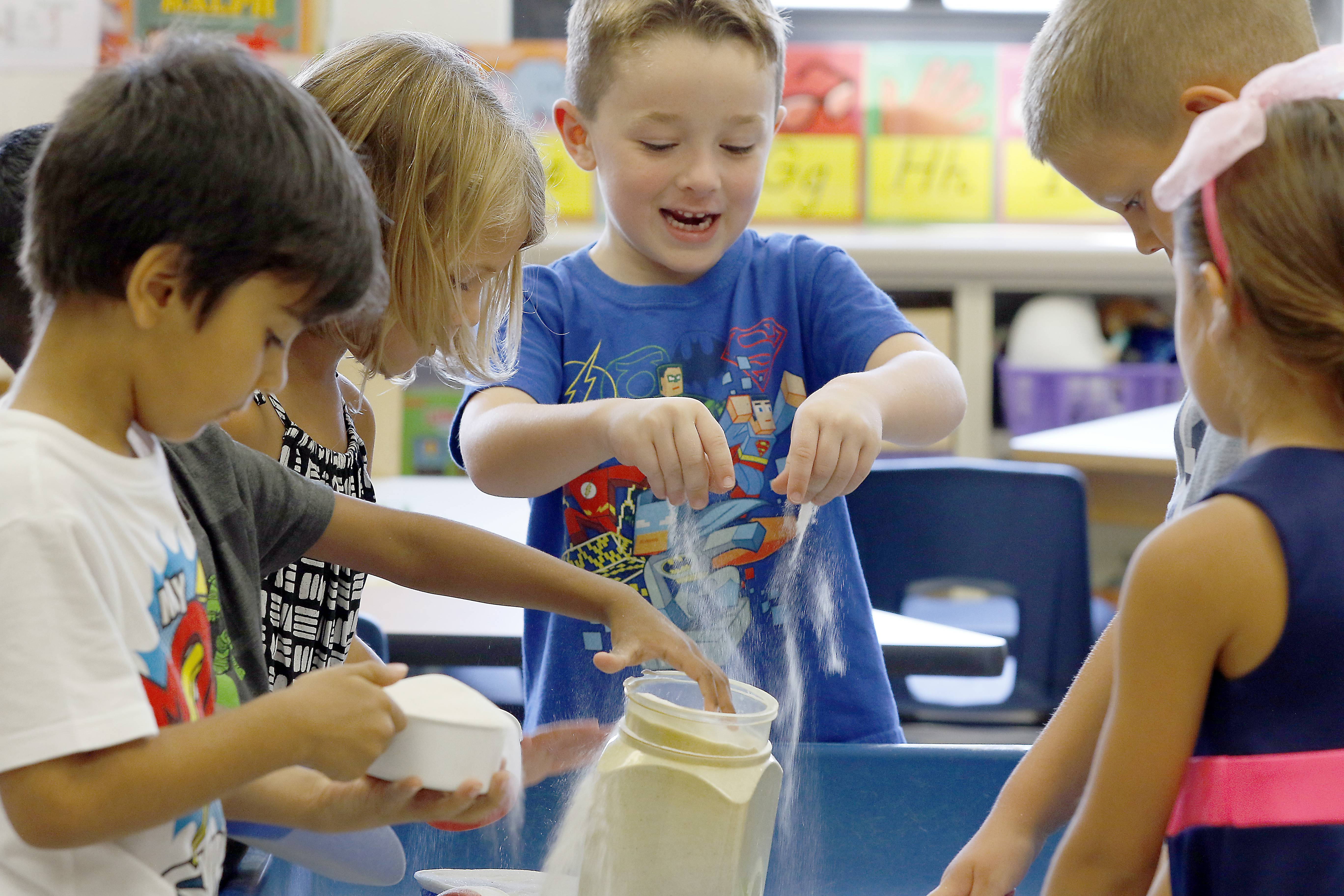 Patrick Murphy and others play with sand in Jan Wilcox's class during the first day of full-day kindergarten last year at Centennial School in Bartlett.