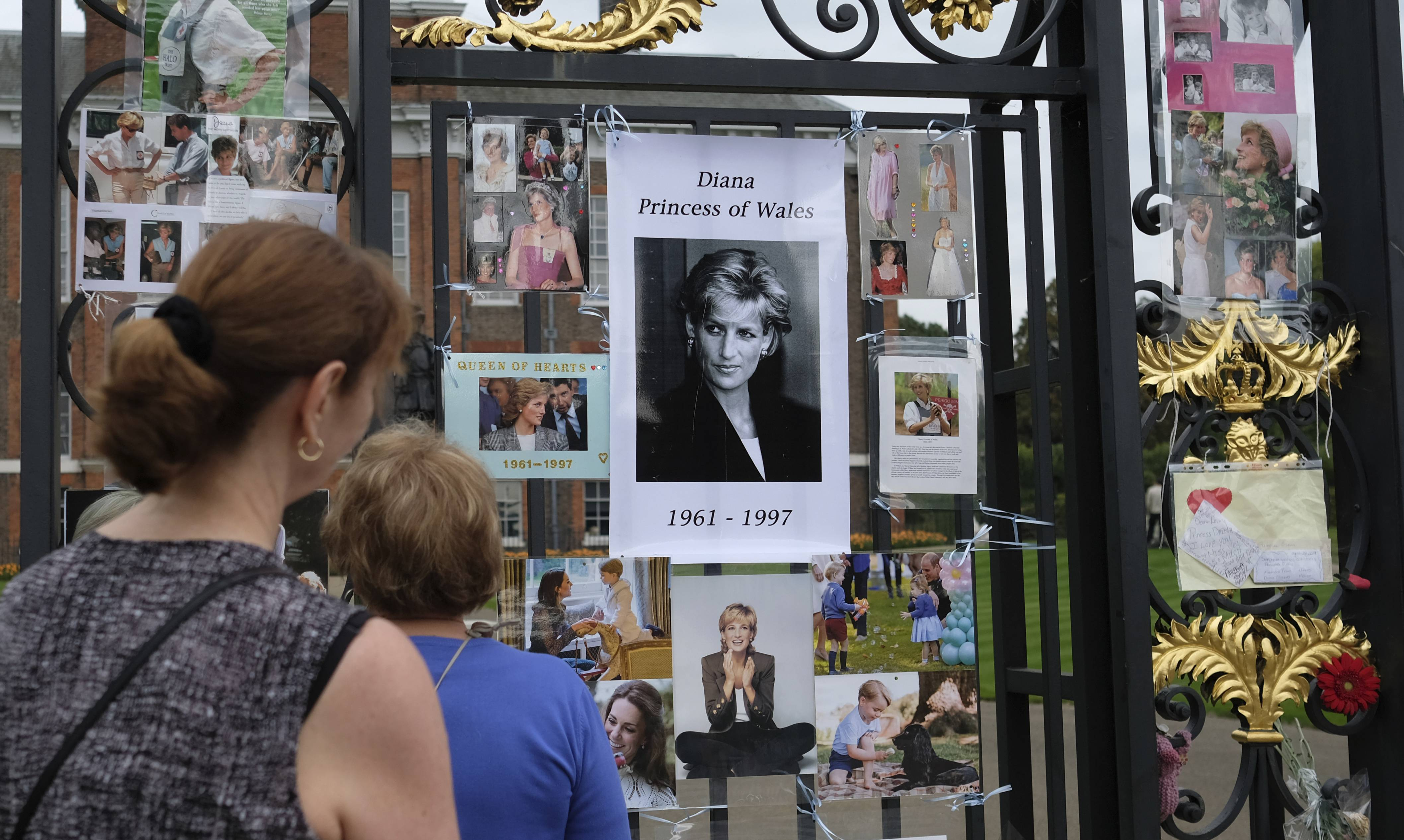 Tourists look at tributes and memorabilia for the late Diana, Princess of Wales outside Kensington Palace in London, Tuesday, Aug. 29, 2017. The tributes are placed on one of the ornamental gates at the palace ahead of the 20th anniversary of Princess Diana's death, in a car crash in Paris Aug. 31, 1997.
