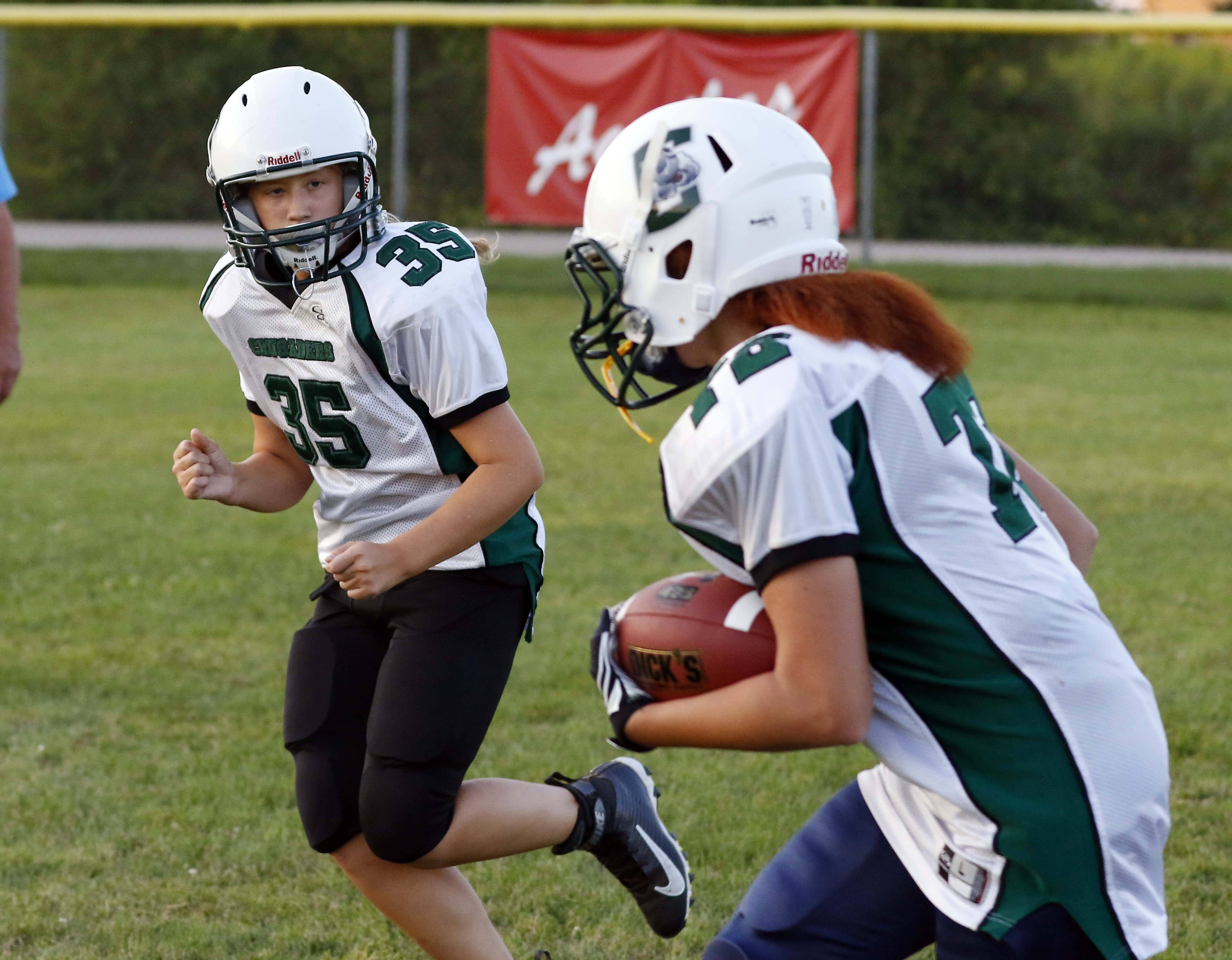 "Zoie Lewis carries the ball while Sophia Olech runs beside her during practice for the Crusaders middle school football team. ""We all work hard and we all like football,"" Lewis said. ""We play together. Nobody has a problem with us."""