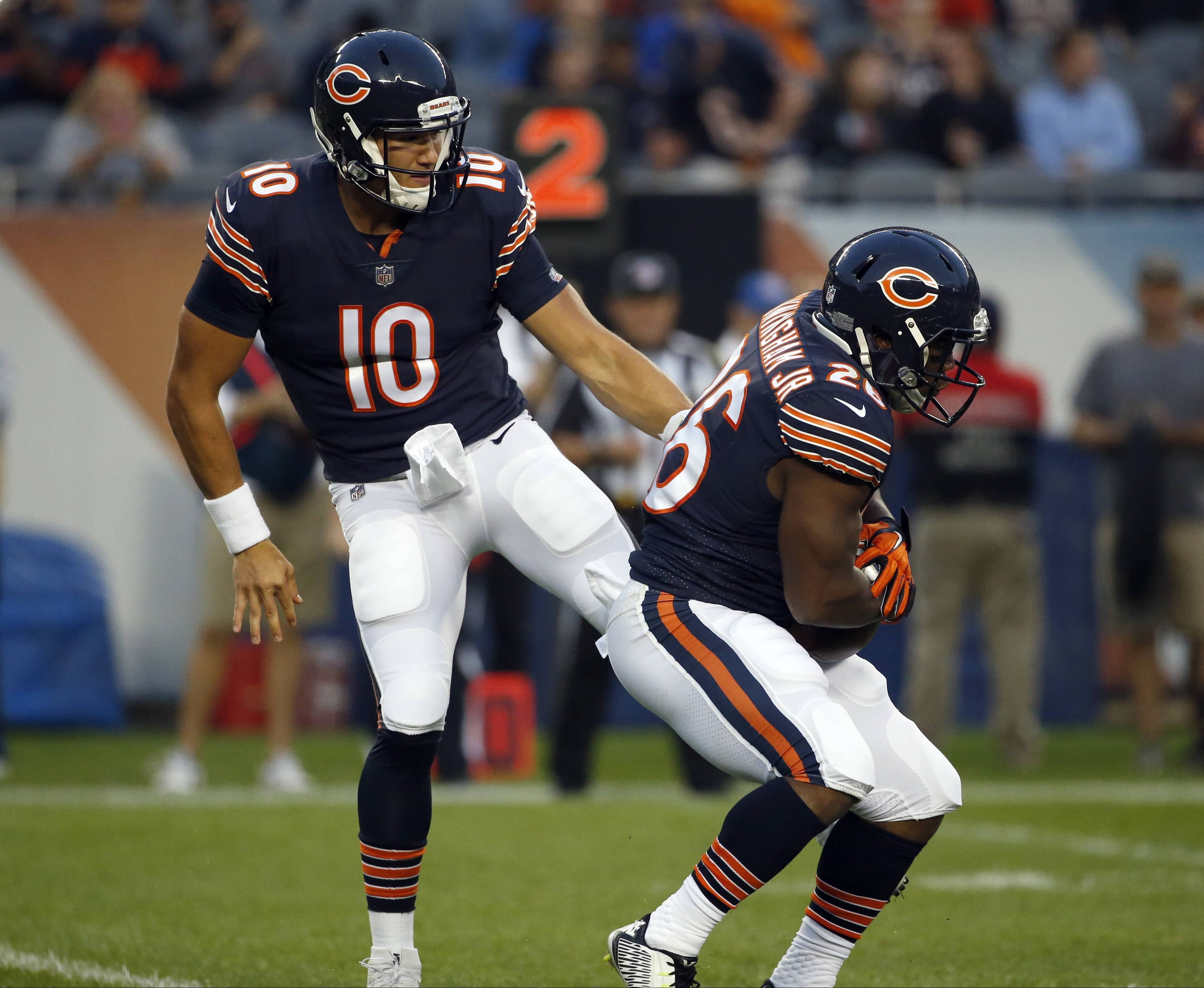 Chicago Bears quarterback Mitchell Trubisky (10) hands off the ball to running back Benny Cunningham (26) during the first half of an NFL football game against the Cleveland Browns, Thursday, Aug. 31, 2017, in Chicago.