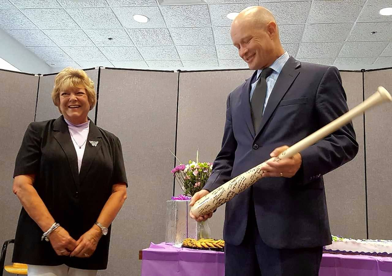 Kane County State's Attorney Joe McMahon presents retiring Administrative Assistant Janet Halsey with a bat signed by lawyers and other staff members. It was the first time the traditional bat was presented to someone other than a departing prosecutor.