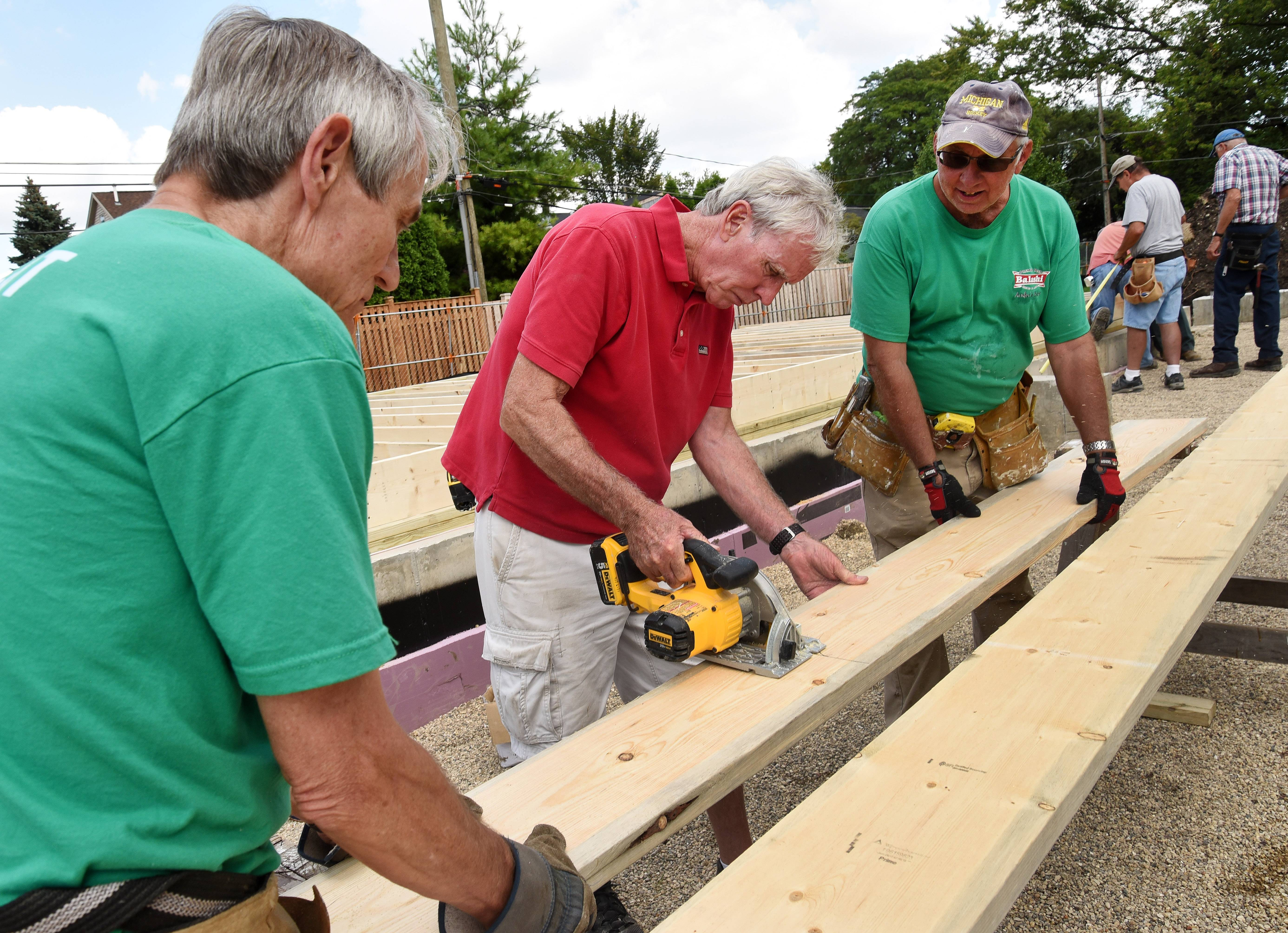 John Wise, lead construction manager, center, of Hoffman Estates, works with Curt Siegel of Palatine, left, and Mike Rekruciak of Elk Grove as work is underway at the first Habitat for Humanity home in Des Plaines.