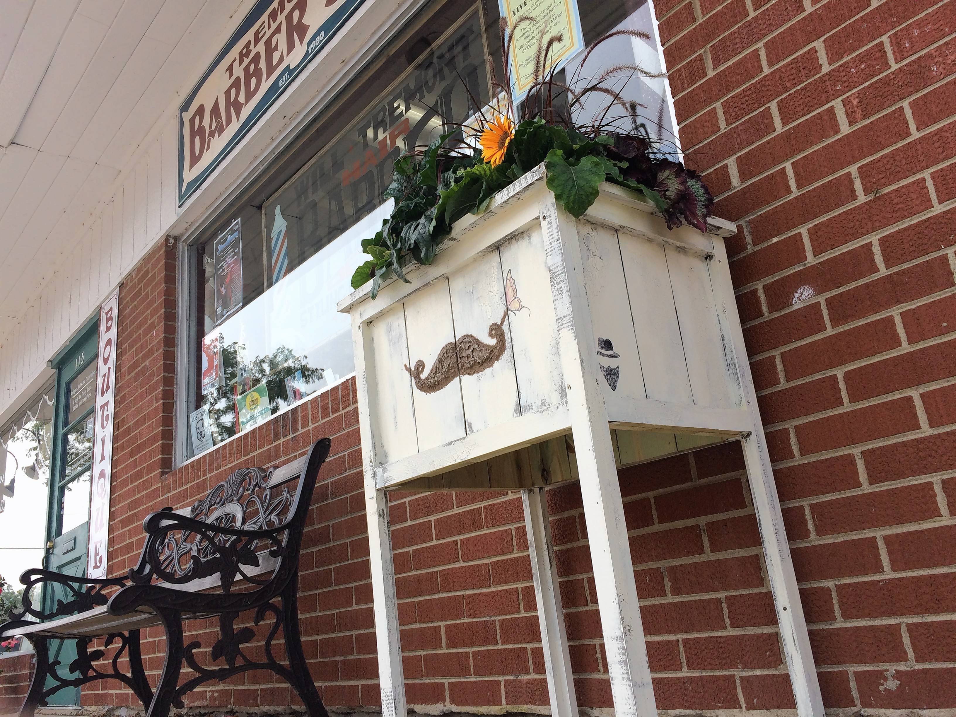 A mustache and a butterfly adorn the planter in front of Tremonte's Barber Shop in downtown Wauconda. Fifteen planters decorate Main Street as part of an annual public art exhibition.