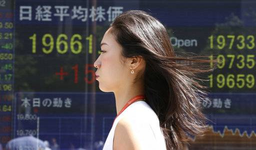 A woman walks by an electronic stock board of a securities firm in Tokyo, Friday, Sept. 1, 2017. Asian shares were mostly higher Friday, taking their cue from optimism on Wall Street set off by a report showing spending by U.S. consumers growing in July, along with wages and salaries. (AP Photo/Koji Sasahara)