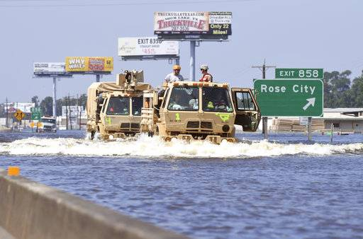 CORRECTS TO REMOVE REFERENCE OF FOOD CART- Military grade vehicles travel west on the east bound lanes of Interstate 10 in north Vidor, Texas, Thursday, Aug. 31, 2017. While several parts of the city are flooded, the northern side received extensive damage. (Guiseppe Barranco/The Beaumont Enterprise via AP)