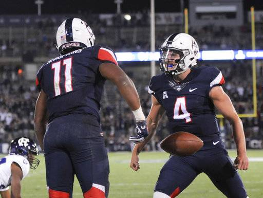Connecticut running back Nate Hopkins (11) is greeted by quarterback Bryant Shirreffs (4) in the end zone after scoring in the fourth quarter of an NCAA college football game against Holy Cross, Thursday, Aug. 31, 2017, in East Hartford, Conn. (AP Photo/Stephen Dunn)