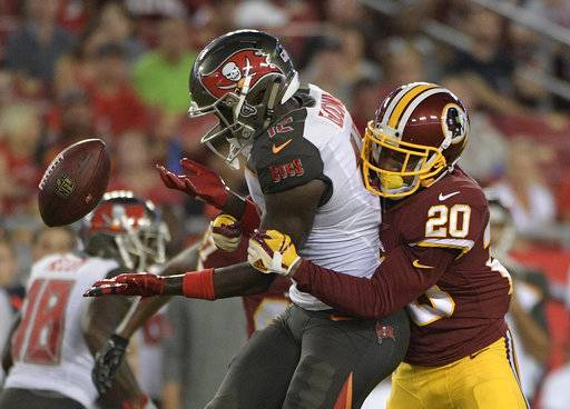 Tampa Bay Buccaneers wide receiver Chris Godwin (12) loses the football after he was hit by Washington Redskins defensive back Joshua Holsey (20) during the second quarter of an NFL preseason football game Thursday, Aug. 31, 2017, in Tampa, Fla. The pass fell incomplete. (AP Photo/Phelan Ebenhack)