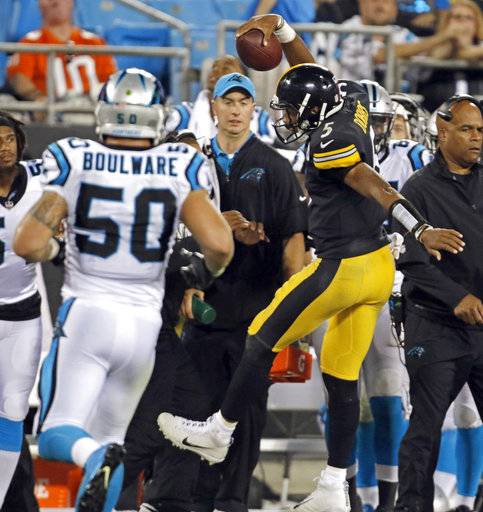 Pittsburgh Steelers' Joshua Dobbs (5) runs out of bounds as he is chased by Carolina Panthers' Ben Boulware (50) in the second half of an NFL preseason football game in Charlotte, N.C., Thursday, Aug. 31, 2017. (AP Photo/Bob Leverone)