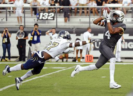 Central Florida wide receiver Tre'Quan Smith (4) catches a pass for a 50-yard touchdown in front of Florida International cornerback Brad Muhammad during the first half of an NCAA college football game, Thursday, Aug. 31, 2017, in Orlando, Fla. (AP Photo/John Raoux)