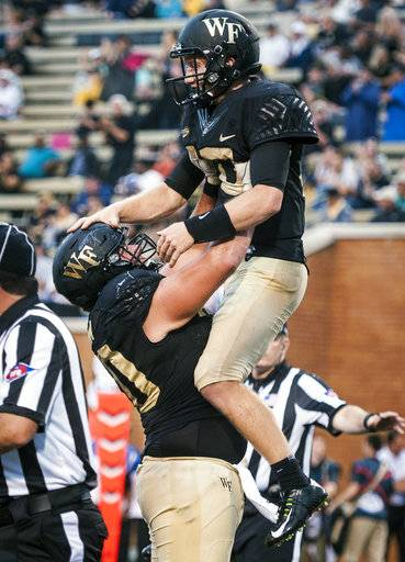 Wake Forest senior quarterback John Wolford (10) is congratulated by offensive lineman Ryan Anderson (70) after running in a touchdown during an NCAA college football game against Presbyterian, Thursday, Aug. 31, 2017, in Winston-Salem, N.C. (Andrew Dye/The Winston-Salem Journal via AP)