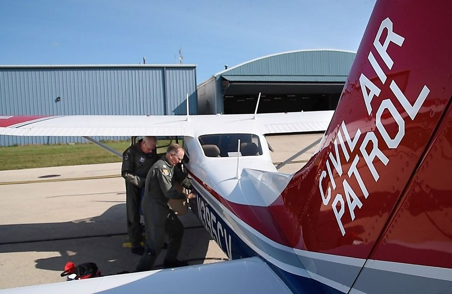 Capt. Rick Jensen, left, of Rockford and Capt. Dave Hooper, of Inverness load equipment before their Civil Air Patrol unit leaves Friday from Lake in the Hills Airport for a six-hour flight to Texas. They will take aerial photographs of the flooding to help the Federal Emergency Management Agency with recovery efforts.