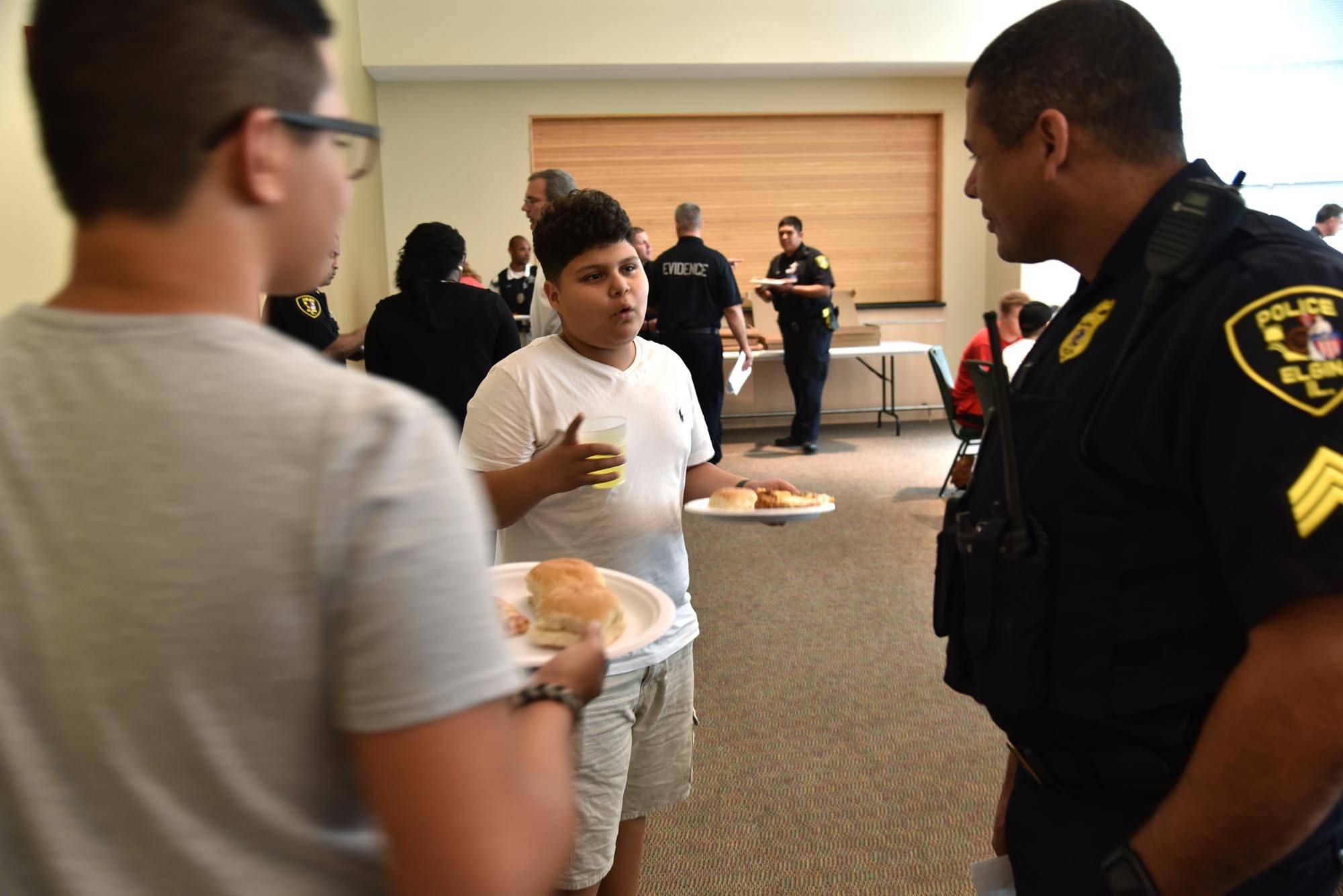 "Kevin Vasquez, 13, of Elgin talks with Sgt. Eric Echevarria during the Elgin Police Department's first ""Teen Summit"" Thursday at the Centre of Elgin. Vasquez says he want to be a police officer."