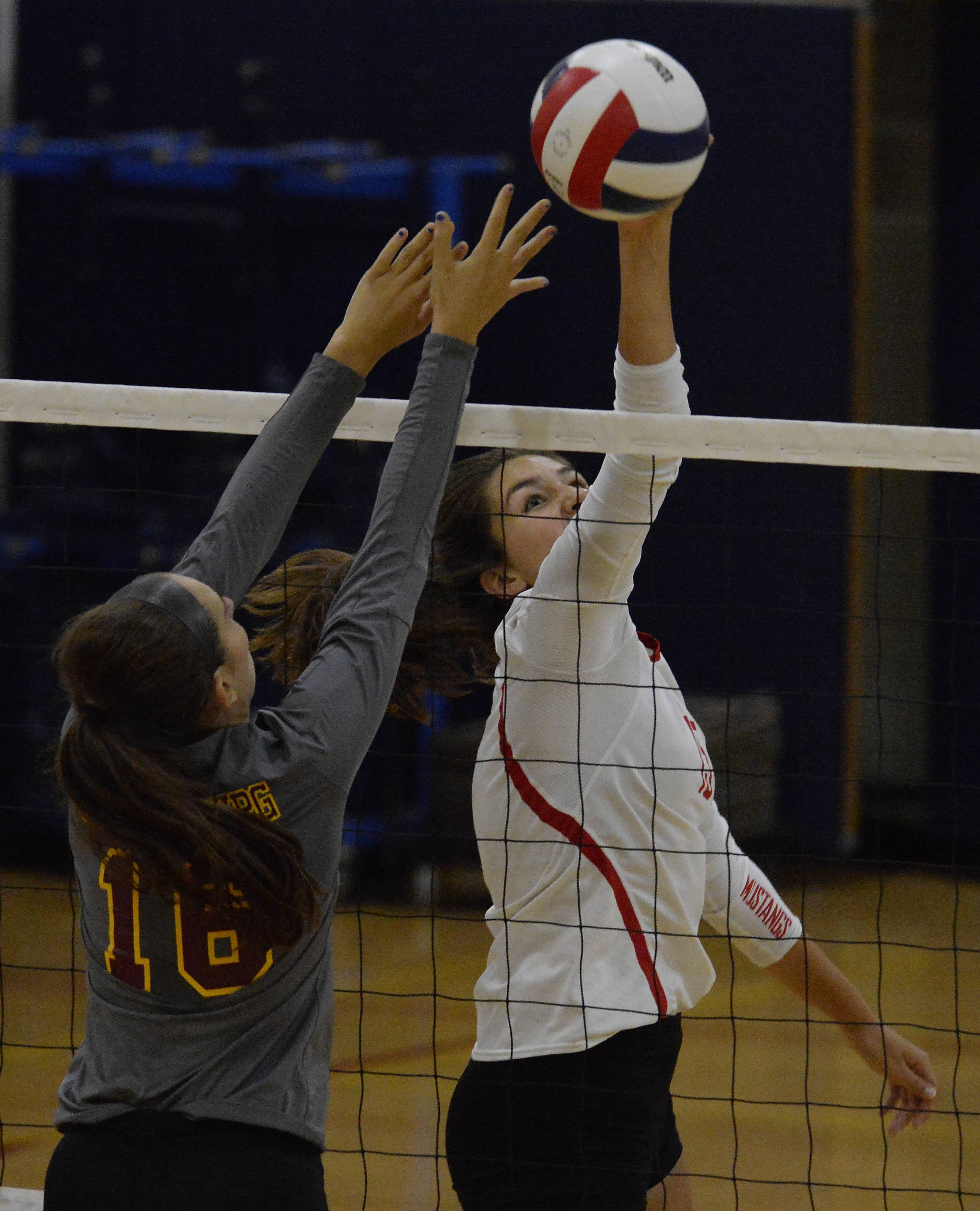 Mundelein's Gillian Paul tips the ball away from Schaumburg's Ari Doroskin during Peggy Scholten Volleyball Classic action Saturday at Conant.