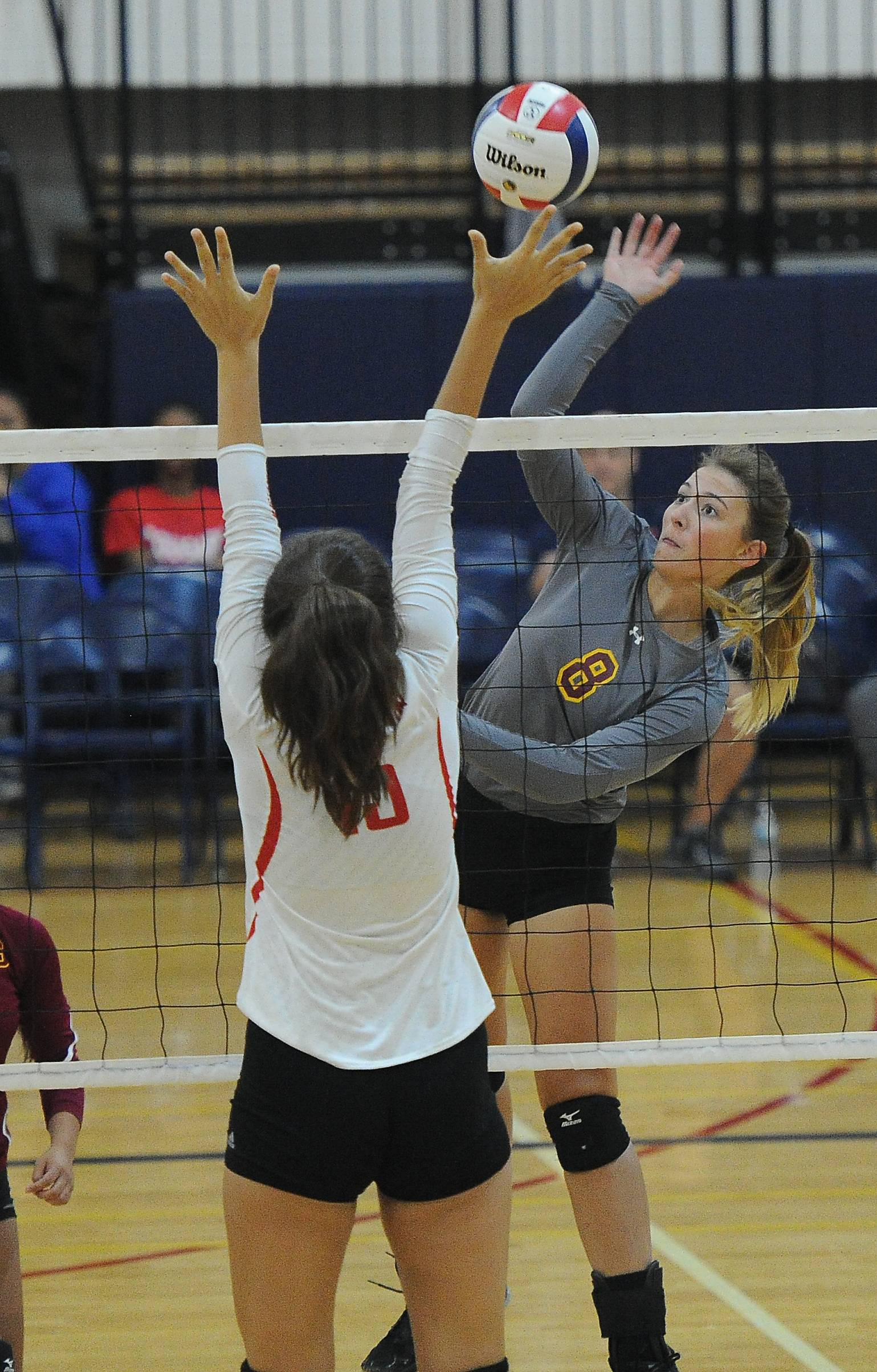 Schaumburg's Natalie Asa smashes the ball into the hands of Mundelein's Faith Krabbe for a block during the Peggy Scholten Volleyball Classic on Saturday at Conant.