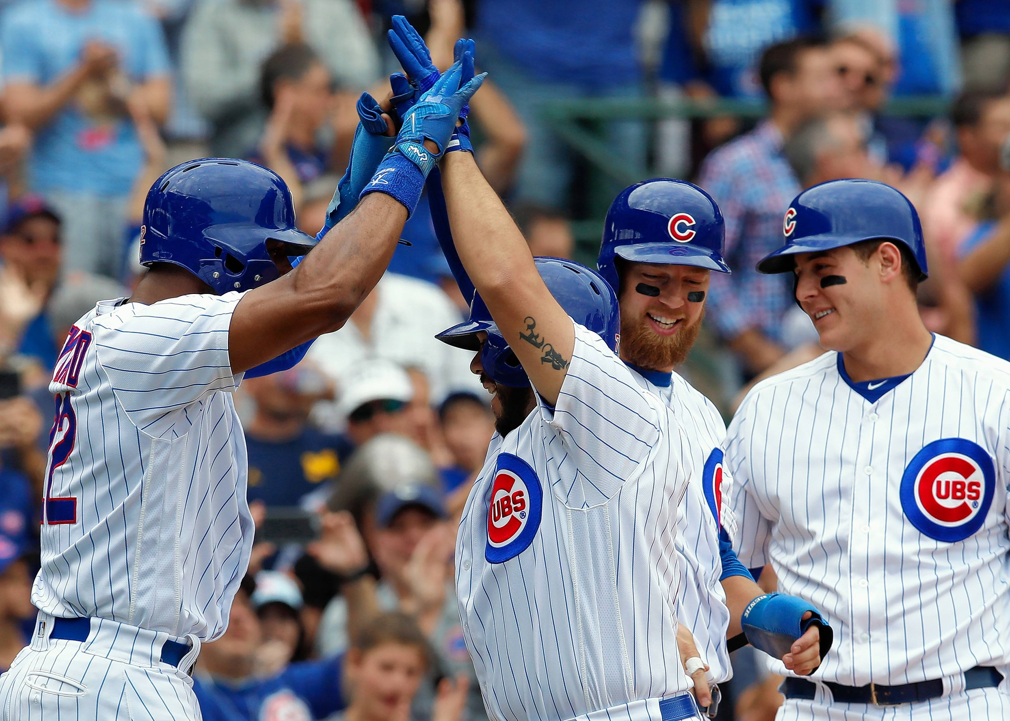 Chicago Cubs' Rene Rivera, second from left, celebrates his grand slam home run against the Atlanta Braves with teammates Jason Heyward, left, Ben Zobrist, second from right, and Anthony Rizzo during the second inning Saturday in Chicago.