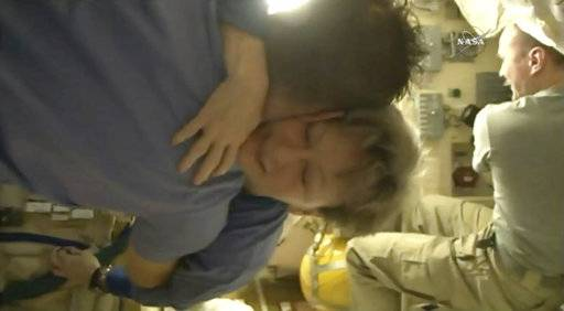 In this image from video made available by NASA, departing astronaut Peggy Whitson hugs Paolo Nespoli aboard the International Space Station during preparations for a return to Earth by her, Jack Fischer and cosmonaut Fyodor Yurchikhin on Saturday, Sept. 2, 2017. (NASA via AP)
