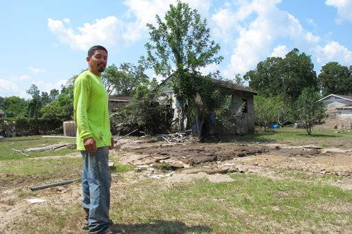 In this photo taken Sept. 1, 2017 in Crosby, Texas, across the San Jacinto River from Houston, Rafael Casas tours his storm ravaged house in a small working-class neighborhood that sits between two Superfund sites, French LTD and the Sikes Disposal Pits. The area was wrecked by Harvey's floods. (AP Photo/Jason Dearen)